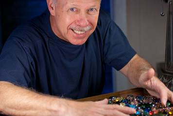 grinning middleaged man greedily grabbing jewelled beads