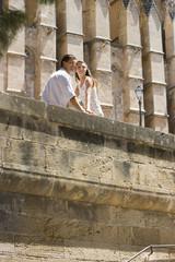 Couple sitting on sunny ledge
