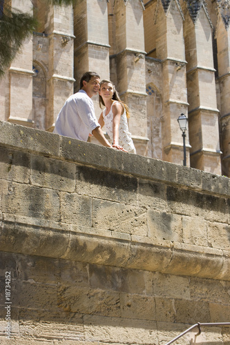 Couple sitting on sunny ledge
