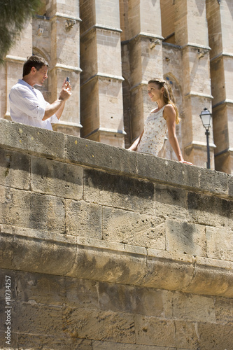 Man taking photograph of woman leaning on ledge