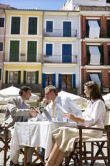Businessmen shaking hands at sunny, outdoor caf