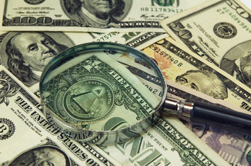 Background from dollar banknotes under a magnifier