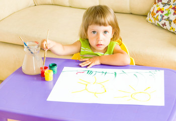 The little girl draws