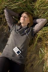 Frau mit MP2 Player liegt laechelnd im Gras und hoert Musik
