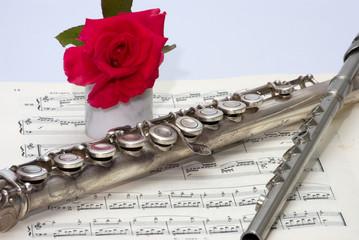 Flauto dolce con rosa, ottavina e spartito musicale