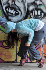young girl against graffiti wall