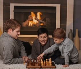 Young family playing chess