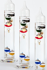 Three water Galileo thermometers with colorful globes in liquid