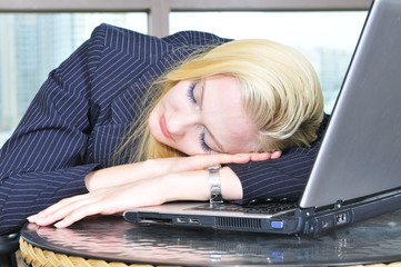 Young tired businesswoman, sleeping on the laptop.