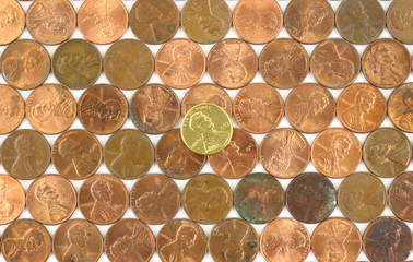 Rows of used pennies with gold penny in the middle