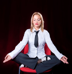 Portrait of business woman meditating on the chair in the office