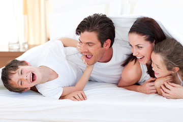 Happy family having fun lying on bed