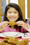 girl eating fried chicken drumstick