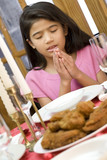 Girl praying during dinner