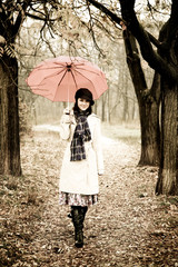 Girl with umbrella at park in rainy day. Photo in vintage style