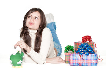Cute girl lying between piggy bank and presents
