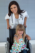 Young female doctor and Smiling girl on a wheelchair with thumb