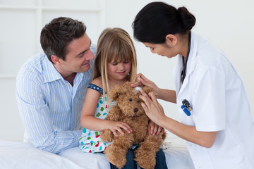 Portrait of a doctor and little girl examing a teddy bear
