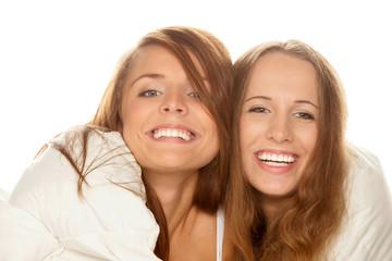 Two smiling teenage girls below duvet
