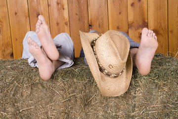 feet and hat on hay