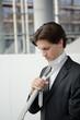 geschäftsmann bindet sich in bürogebäude krawatte,bewerbung