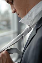 geschäftsmann bindet sich in bürogebäude krawatte
