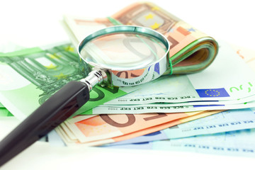 euro notes with magnifier on white background