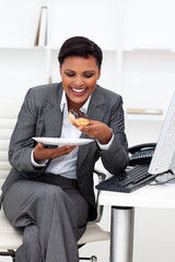 Happy businesswoman eating in the office