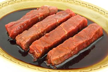 Steak strips marinating in balsamic vinegar