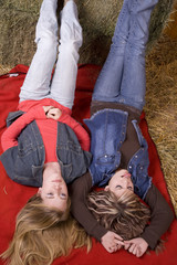 girls laying on red blanket one tongue