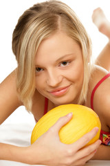 Young happy woman with yellow melon