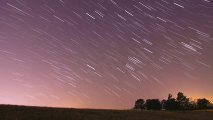Star trails over landscape with light pollution