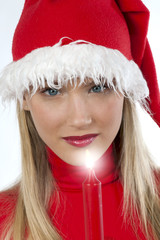 Beautiful young woman in santa's hat holding a red candle