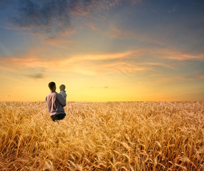 man in wheat field with boy
