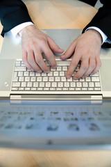 hände von manager tippen auf laptoptastatur in büro