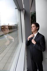 geschäftsmann kontrolliert krawatte in spiegelnder scheibe