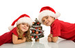 Happy kids with santa hats and small christmas tree