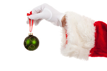 Santa's hand holding a green Christmas ornament