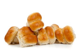 Golden baked dinner rolls on a white background