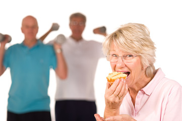Mature lady eating cake at the gym