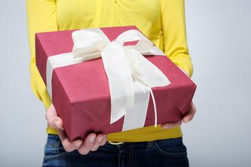 Geschenk in den Haenden einer jungen Frau