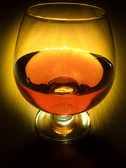 Glass of brandy over wooden background on dark