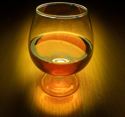 Glass of brandy with light on dark