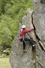 Frau klettert am senkrechten Fels