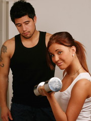 Girl lifting weight in gym, man in background