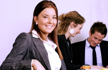 Girl in office smiling, colleagues in background