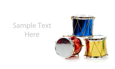 Miniature Christmas drums on white with copy space