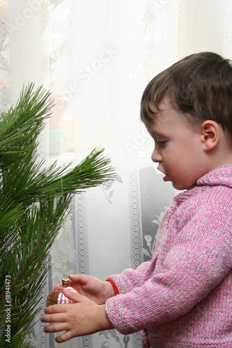 The little boy hangs up an ornament on a Christmas fur-tree