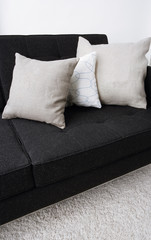 indoor setting, gray pillows laying on a black sofa