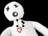 voodoo doll with pins in its heart